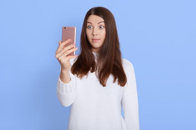 Foto van verrast donkerharige vrouw draagt witte trui, houdt mobiele telefoon vast, krijgt bericht, kijkt met geschokte uitdrukking op het scherm van de mobiele telefoon, vormt binnen geïsoleerd