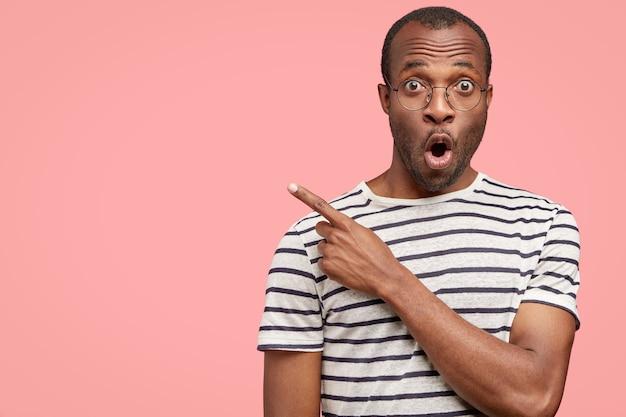Foto van verrast emotionele zwarte man geeft aan met wijsvinger opzij