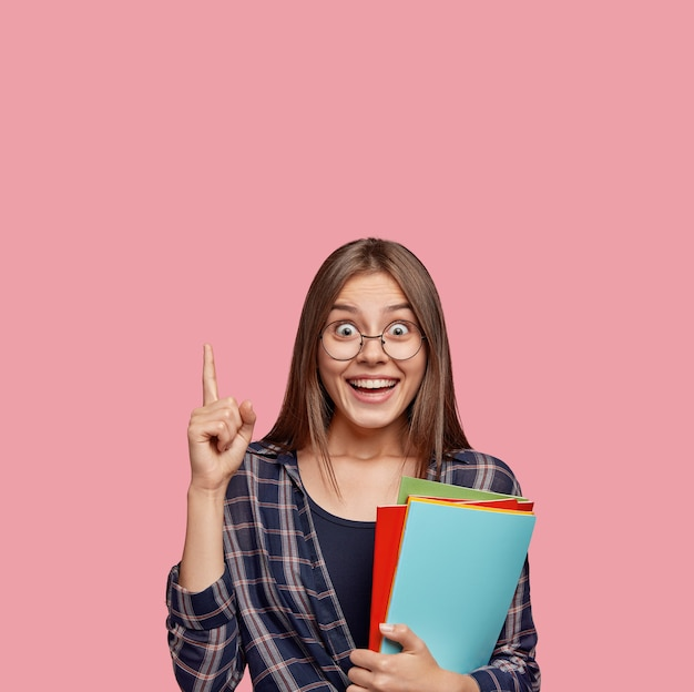Foto van verrast europese vrouw wijst met wijsvinger naar boven, in goed humeur