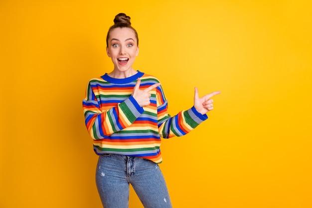 Foto van verrast meisje promotor punt wijsvinger copyspace onder de indruk advertentie promotie aanbevelen suggereren keuze keuze dragen pullover geïsoleerd glans kleur achtergrond
