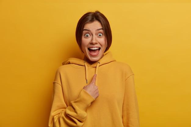 Foto van verrast opgewonden vrolijke jonge vrouw wijst naar zichzelf, gelooft niet in gekozen te worden als leider, draagt casual sweatshirt, geïsoleerd over gele muur. selectieve aandacht. wie, ik?