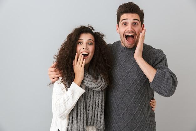 Foto van verrast paar man en vrouw schreeuwen en aanraken van gezicht, geïsoleerd over grijze muur