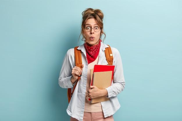 Foto van verrast schoolmeisje houdt blocnotes, klaar voor school en studeren, draagt rugzak