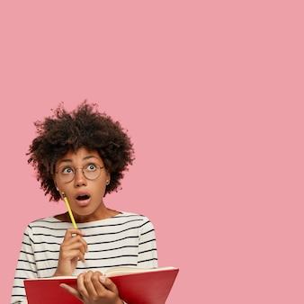 Foto van verrast schoolmeisje met donkere huid heeft verbaasde blik naar boven geschokt, mond wijd opengehouden