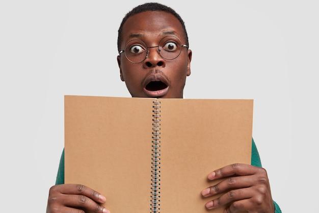 Foto van verrast zwarte man houdt geopende spiraal kladblok vooraan voor het vastleggen van informatie, draagt een transparante bril, houdt de mond open