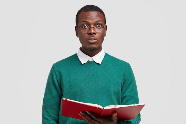 Foto van verrast zwarte mannelijke leraar kijkt rechtstreeks naar de camera, draagt een bril, draagt kladblok met notities, voert lezing