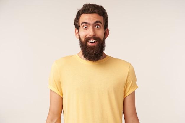 Foto van verraste knappe, bebaarde jonge kerel, emotie verrast of verbluft staand