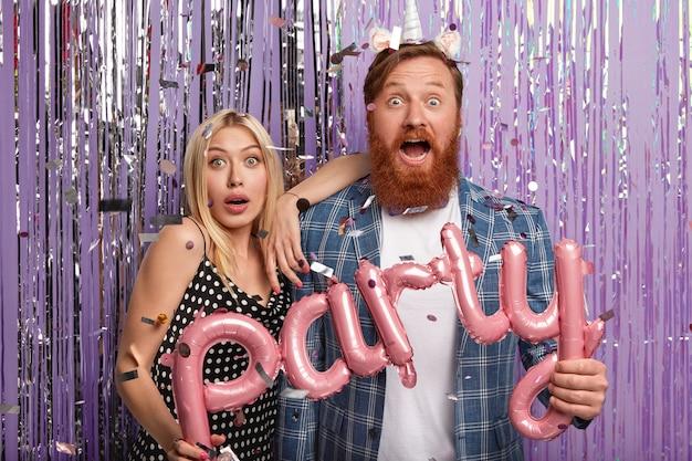 Foto van verraste vriendin en vriend hebben verbaasde uitdrukkingen, houden briefvormige ballonnen vast