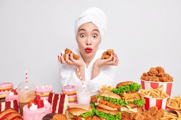 Foto van verraste vrouw houdt gebakken kip vast, omringd door fastfood