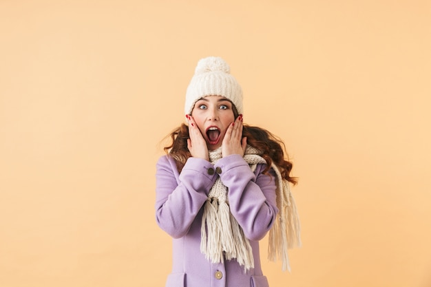 Foto van verraste vrouwen20s die in de winterkleren schreeuwen, terwijl status geïsoleerd