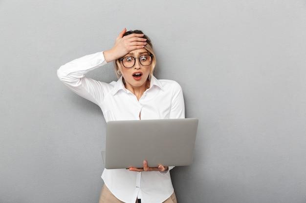 Foto van verraste zakelijke vrouw die een bril draagt en laptop op kantoor houdt, geïsoleerd