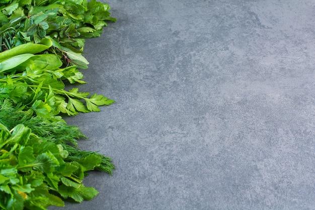 Foto van verse gezonde groene bladeren op stenen achtergrond.