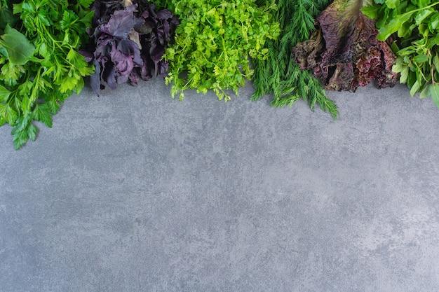 Foto van verse gezonde groene groenten op stenen achtergrond.