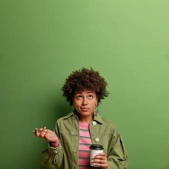 Foto van verwarde aarzelende jonge vrouw werpt palm in verbijstering en geconcentreerd boven, drinkt afhaalkoffie, staat binnen, draagt modekleding, geïsoleerd op groene muur, kopieer ruimte