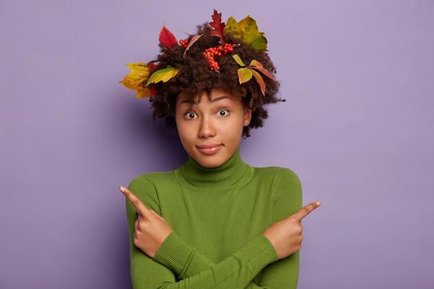 Foto van verwarde donkere vrouw met herfstbladeren in het haar, kruist handen over de borst, zijwaarts wijst, draagt groene trui, geïsoleerd op paarse achtergrond.