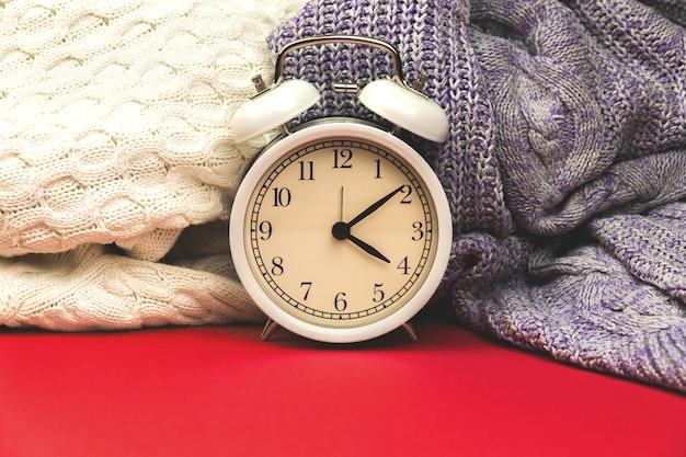 Foto van vintage wekker op gezellige huiscomfortachtergrond van warme gebreide truien