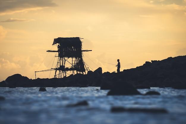 Foto van visser op zoek naar vis aan zee in de ochtend, wat gebruikelijk is in thailand