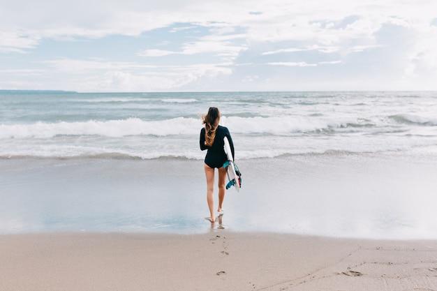 Foto van volledige lengte van achterkant van aantrekkelijke jonge vrouw met lang haar gekleed in zwembroek loopt in de oceaan met een surfplank, achtergrond de oceaan, sport, actieve levensstijl