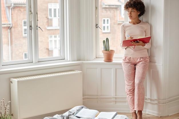 Foto van volledige lengte van bedachtzame ondernemer in nachtkleding, maakt aantekeningen van werkplan in notitieblok, kijkt peinzend opzij, staat in ruime kamer bij raam.