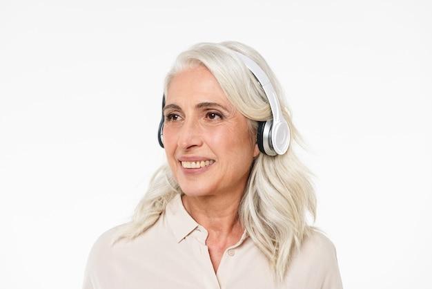 Foto van volwassen vrouw 60s met grijs haar glimlachend met perfecte tanden en opzij kijken terwijl u luistert naar muziek via draadloze hoofdtelefoons, geïsoleerd over witte muur