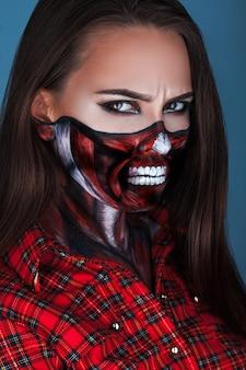 Foto van volwassen vrouw met schrikken mae voor halloween-nacht in studio