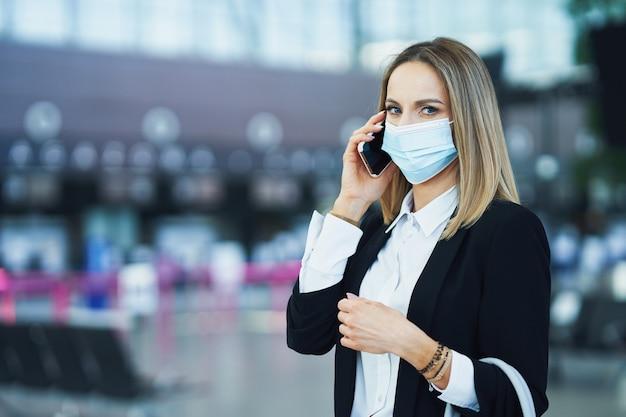 Foto van volwassen vrouwelijke passagier die smartphone gebruikt op de luchthaven