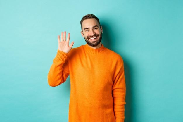 Foto van vriendelijke jongeman die hallo zegt, glimlachend en zwaaiend met de hand, je begroet, staande in een oranje trui over een lichtturkooise muur.
