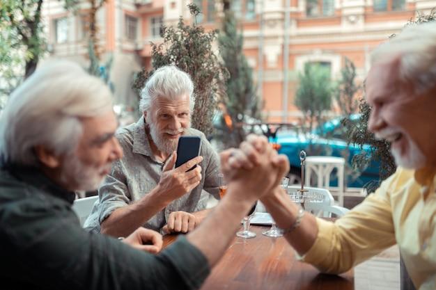 Foto van vrienden. grijsharige man maakt foto van vrienden die armworstelen terwijl hij buiten de pub zit