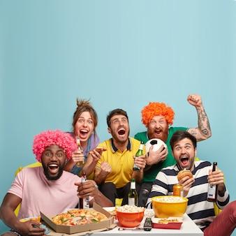 Foto van vrienden kijken naar voetbalwedstrijd, vieren het doel, balken vuisten, kijken naar sportwedstrijden, hebben een heerlijke snack, drinken koud bier, brengen vrije tijd thuis door. tijdverdrijf en vermaak