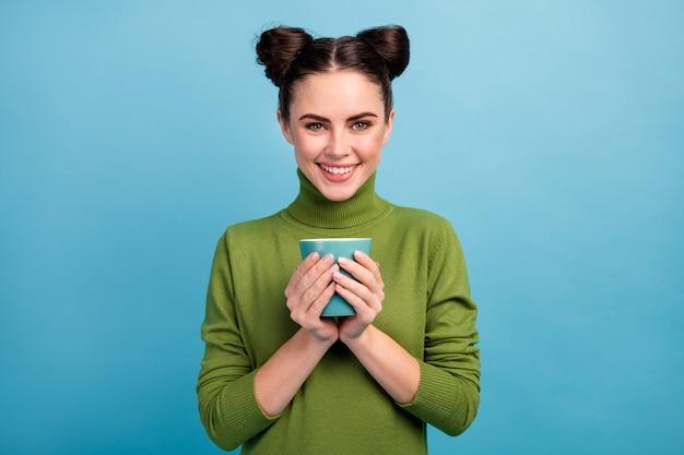 Foto van vrij aantrekkelijk charmant dame tiener houden warme drank kopje thee koffie genieten ochtend dragen warme groene coltrui trui geïsoleerde blauwe kleur muur