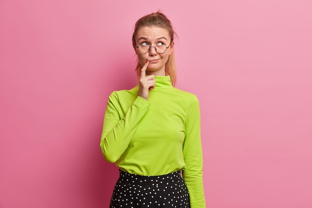 Foto van vrij doordachte vrouw houdt vinger in de buurt van lippen heeft gezichtsuitdrukking verward