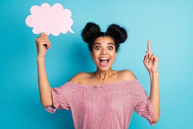 Foto van vrij funky donkere huid dame vasthouden leeg papier wolk vinger opsteken creatieve toespraak inspiratie dragen gestreept rood wit off-schouders blouse geïsoleerd blauwe kleur muur