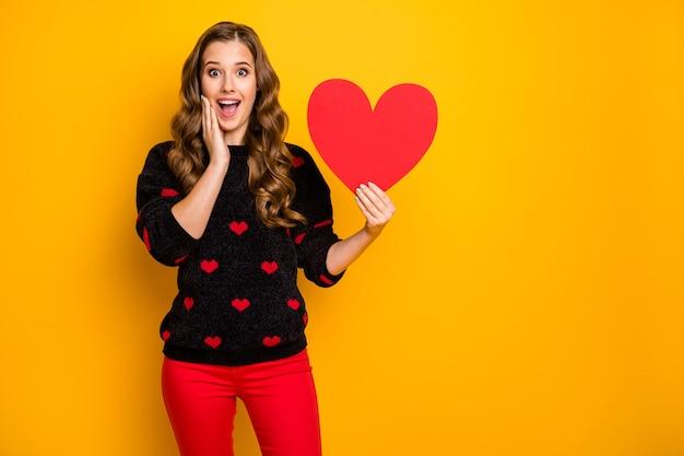 Foto van vrij geschokt krullend dame amour greep groot papieren hart demonstreren creatieve briefkaart datum uitnodiging slijtage harten patroon trui rode broek