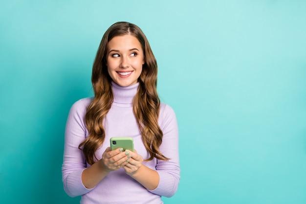 Foto van vrij grappige dame houden telefoon schrijven creatieve blogpost kijken zijkant lege ruimte geïnteresseerd dragen paarse trui coltrui geïsoleerd groenblauw blauw pastelkleur