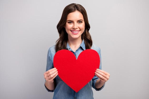 Foto van vrij grappige dame houdt groot rood papier hart vieren liefhebbers dag creatieve uitnodiging voor vriendje dragen casual jeans denim overhemd geïsoleerde grijze kleur