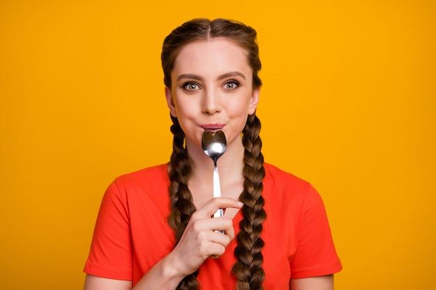 Foto van vrij grappige hongerige dame houdt metalen lepel in de mond