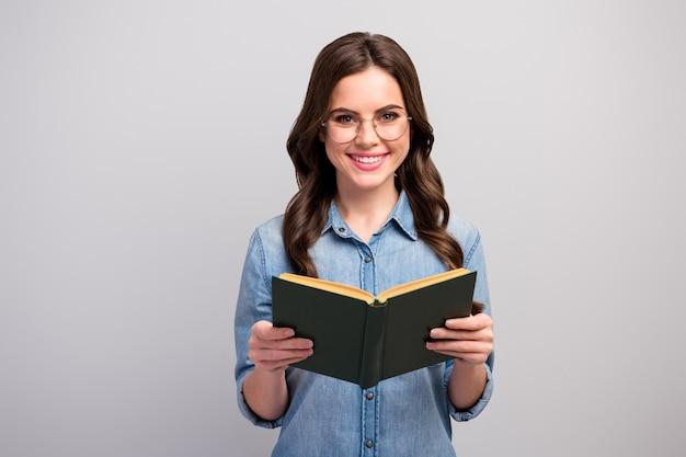 Foto van vrij grappige zakelijke dame boek handen lezer toothy stralend glimlachen goed humeur slijtage specs casual jeans denim overhemd geïsoleerde grijze kleur