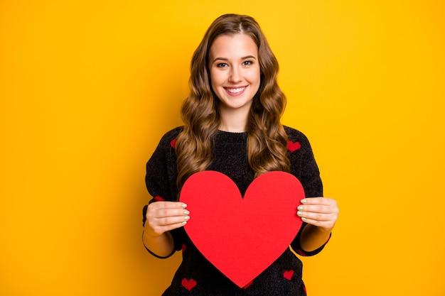 Foto van vrij krullend lang kapsel dame met groot papieren hart creatief idee briefkaart dragen zwart rode harten patroon trui demonstreren