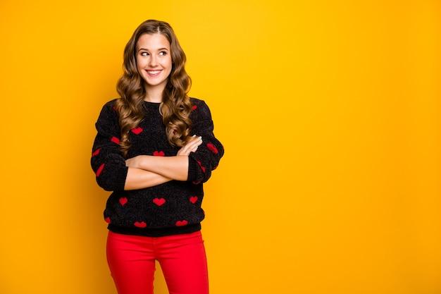 Foto van vrij krullend lang kapsel dame zelfverzekerd armen oversteken goed humeur kijken zijkant lege ruimte dragen zwarte rode harten patroon trui broek