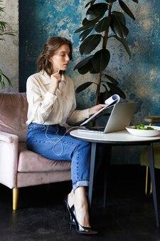 Foto van vrij mooie jonge vrouw zitten in café binnenshuis met behulp van laptop met documenten praten via de mobiele telefoon.