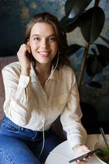 Foto van vrij mooie jonge vrouw zitten in café binnenshuis praten via de mobiele telefoon.
