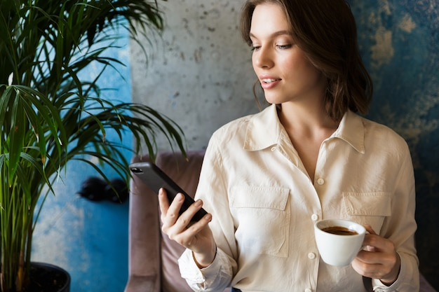 Foto van vrij mooie jonge vrouw zitten in café binnenshuis werken koffie drinken met behulp van mobiele telefoon.