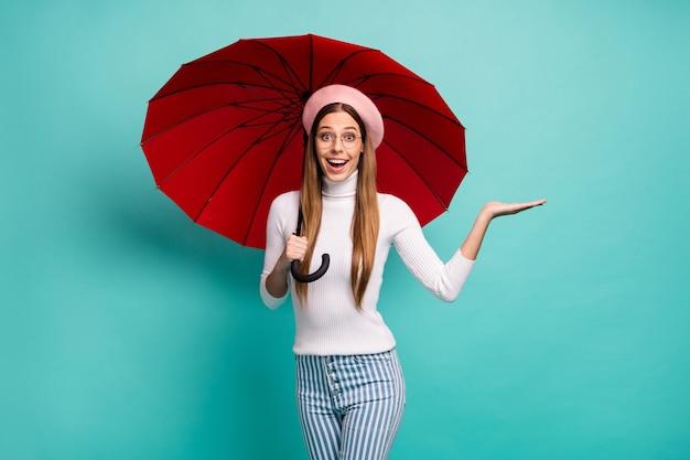 Foto van vrij opgewonden dame houdt grote rode paraplu vast, houd open arm nieuwigheid advertentie product lage prijs aanbieding draag specificaties roze baret witte coltrui gestreepte jeans geïsoleerd groenblauw kleur achtergrond