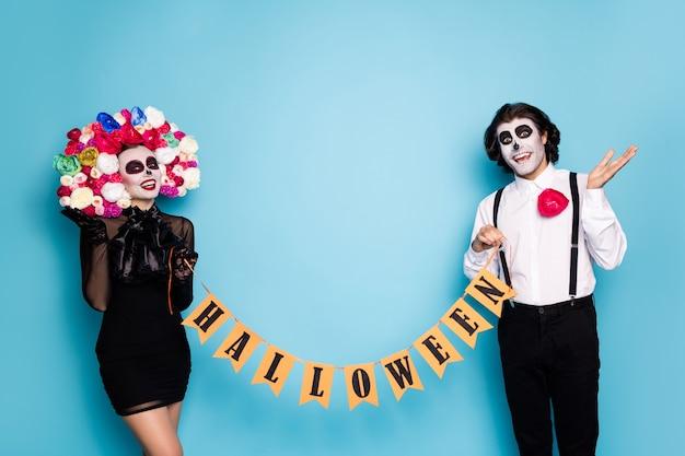 Foto van vrij spookachtig paar man dame houd gemarkeerd lint uitnodigen gasten service thema evenement dragen zwarte korte mini jurk dood kostuum rozen hoofdband bretels geïsoleerde blauwe kleur achtergrond