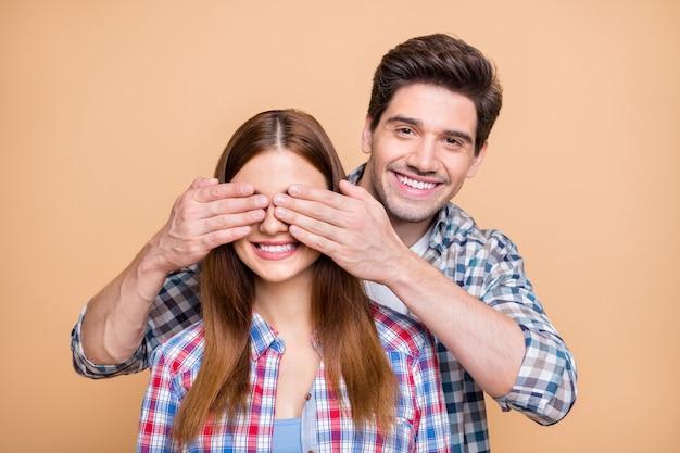 Foto van vrolijk charmant schattig positief paar meisje en jongen met tweede bereid zijn geliefde te verrassen gissen wie haar ogen bedekt geïsoleerd op beige pastel kleur achtergrond