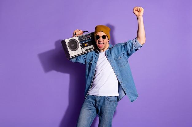 Foto van vrolijk extatisch schreeuwen schreeuwen gelukkige kerel met retro-recorder die hij zojuist heeft gewonnen, gekocht tijdens de verkoop geïsoleerd over paarse violette levendige kleurenachtergrond