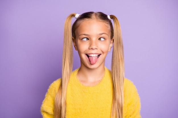 Foto van vrolijk grappig belachelijk meisje steekt haar tong uit waardoor ogen naar elkaar kijken geïsoleerde violet pastel kleur muur