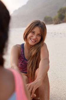 Foto van vrolijk kaukasisch meisje heeft vriendelijke charmante glimlach