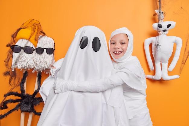 Foto van vrolijk klein kind omarmt geest heeft leuke dwazen rond poses op oranje