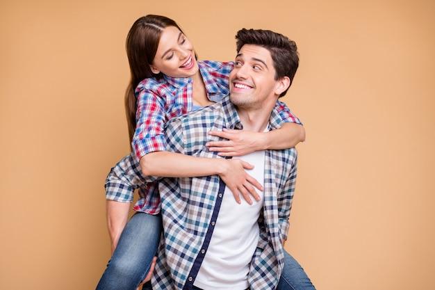 Foto van vrolijk positief schattig charmant leuk paar meeliften dragen geruit overhemd jeans denim knuffelen man met zijn meisje geïsoleerd op beige pastel kleur achtergrond
